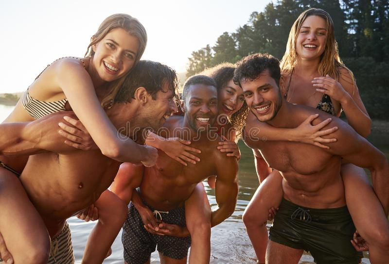 Three young adult couples piggy backing in a lake, close up royalty free stock photo