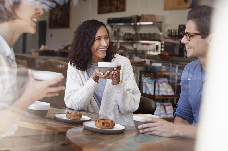 Three young adult friends talking, drinking coffee at cafe royalty free stock photography