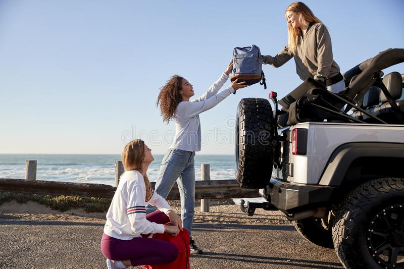 Three young adult girlfriends unloading backpacks from a car stock photos