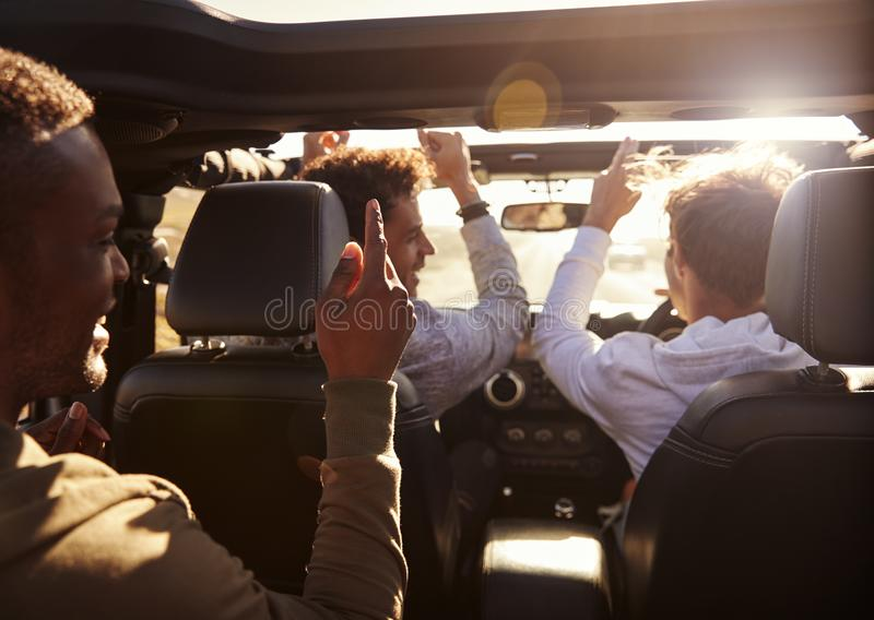 Three young adult men having fun driving an open top car royalty free stock images