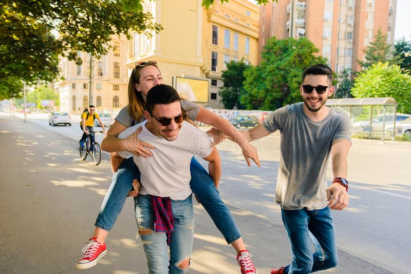 THREE YOUNG ADULTS TAKING LEISURELY WALK THROUGH THE CITY stock image