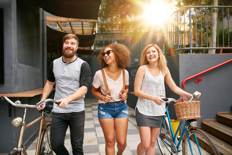 Three young adults walking together with bike royalty free stock photos
