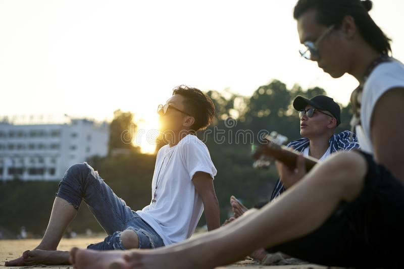 Three young asian men sitting on beach stock photo