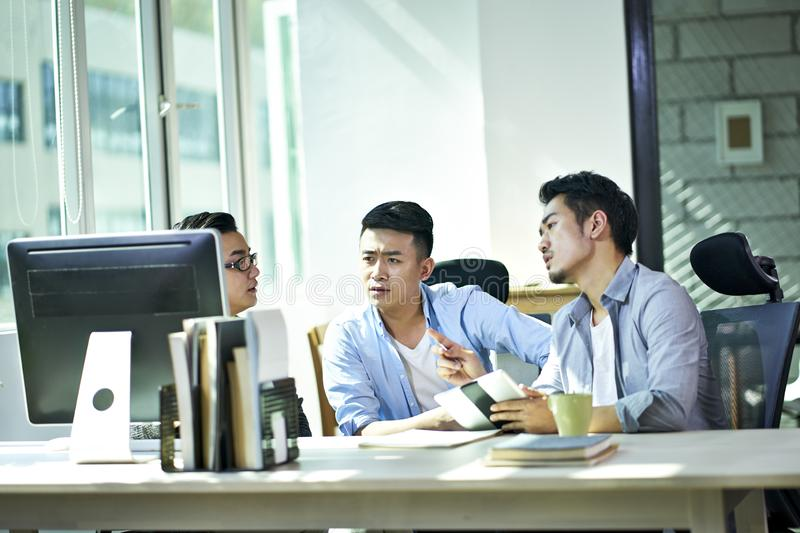Three young asian entrepreneurs discussing business in office stock photos