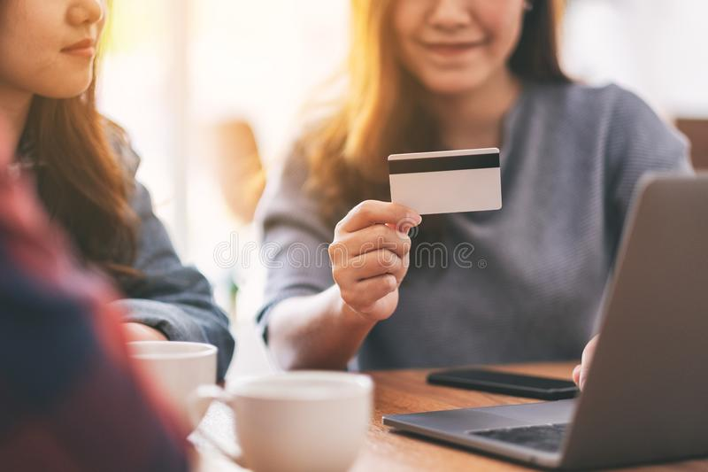 Asian people use credit card to purchasing and shopping online. Three young asian people use credit card to purchasing and shopping online royalty free stock image