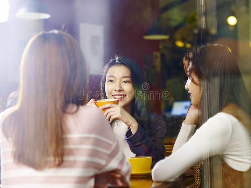 Three young asian women chatting talking in coffee shop royalty free stock photos