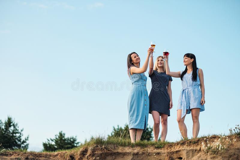 Three young attractive women, in blue dresses are walking along the seashore. Girlfriends communicate, laugh and drink royalty free stock images