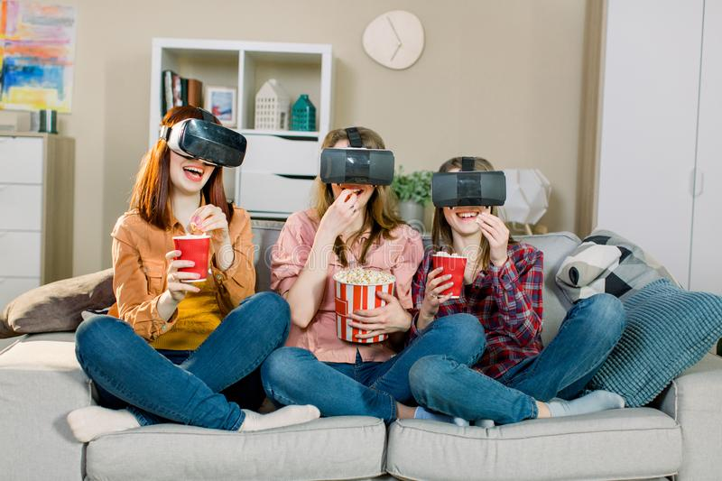 Three young attractive women wearing headset VR virtual reality vision goggles watching video, sitting on the sofa and royalty free stock photos