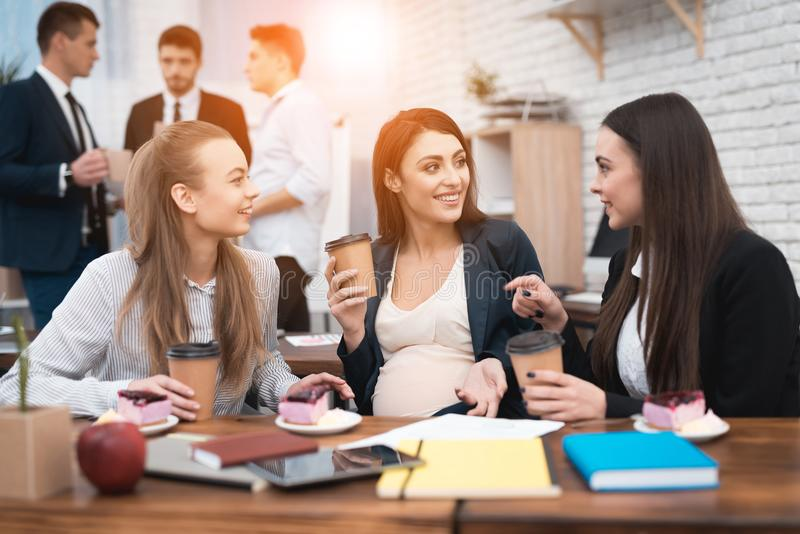 Three young beautiful girls socialize drinking coffee and eating cakes in the office. Young pregnant women with girlfriends drinking latte at lunch break royalty free stock photography