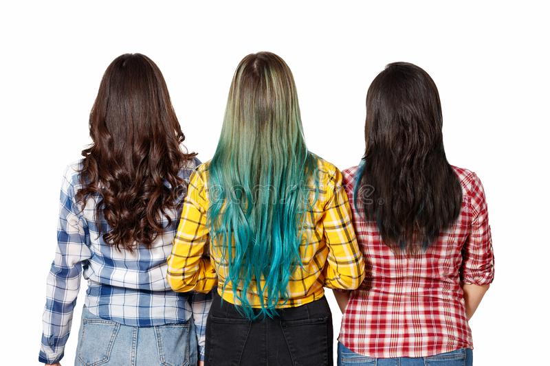 Three young beautiful women girls with beautiful long hair stand next to the view from the back. isolated on white background stock photo