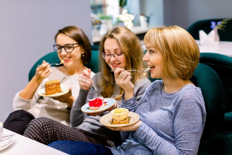 Three young beautiful Women sitting on the sofa in cafe indoors and Having lunch In Cafe. Women eating cakes and having. Fun royalty free stock image