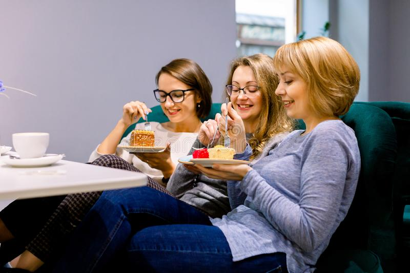 Three young beautiful Women sitting on the sofa in cafe indoors and Having lunch In Cafe. Women eating cakes and having. Fun stock photos