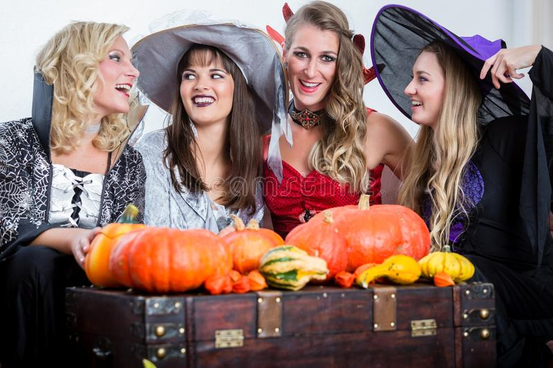 Three beautiful women acting as witches joining their malicious. Three young and beautiful women wearing funny party costumes while acting as witches joining royalty free stock photography