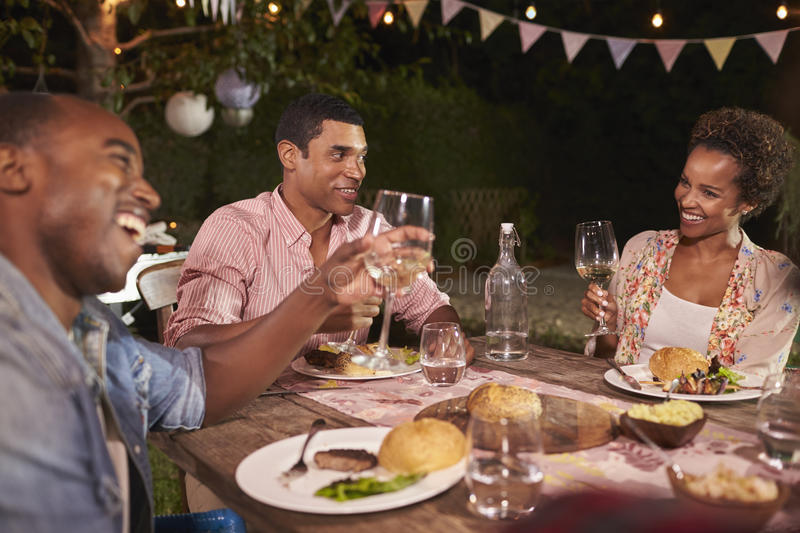 Three young black adults enjoying a garden dinner party royalty free stock images