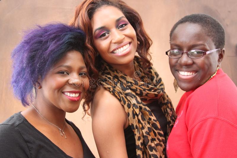 Three young black women together smiling. Three young black women smiling at the camera stock image