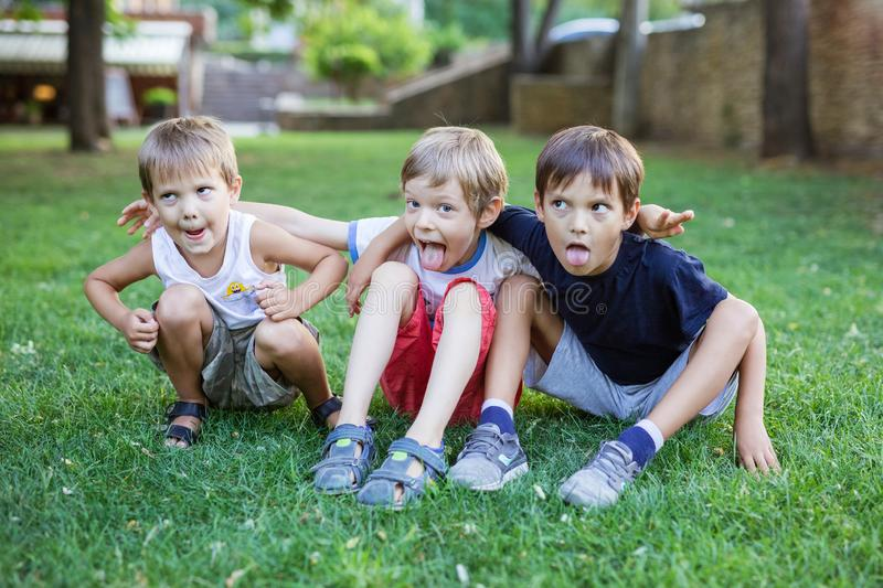 Three young boys making weird grimace faces in summer park royalty free stock photo