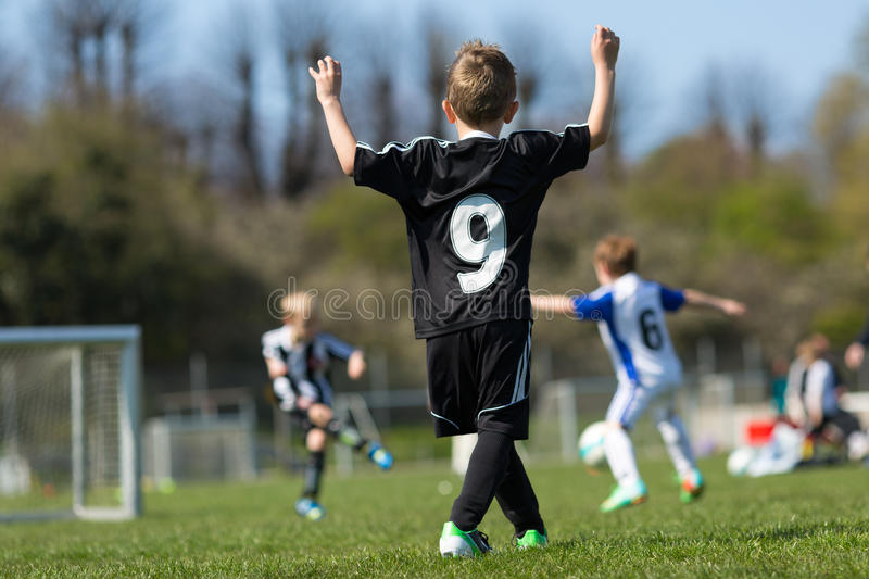 Three young boys playing soccer stock images