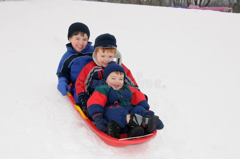 Three young boys sledding downhill together