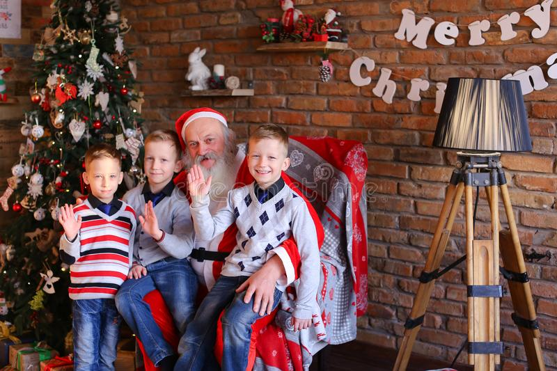 Three young boys tell Santa Claus funny stories in decorated in stock image