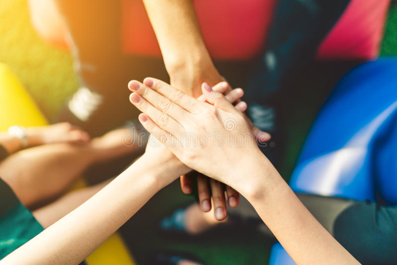Three young business people joining hands team up, teamwork or unity concept. Multi-ethnic diversity group, warm light and depth of field effect royalty free stock photography