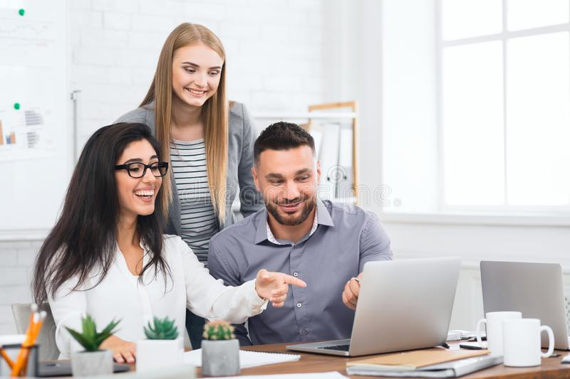 Three young business people looking at laptop stock image