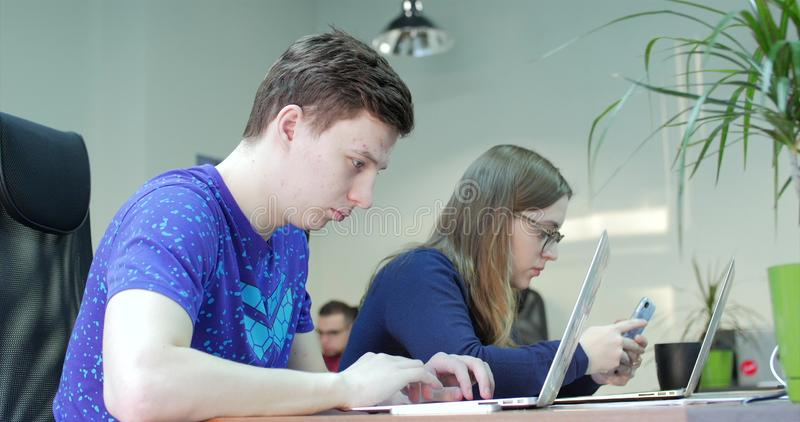 Three Young Business People Using Computer in the Office. Two Decorator`s Colleagues Working Together on an Innovative stock photography