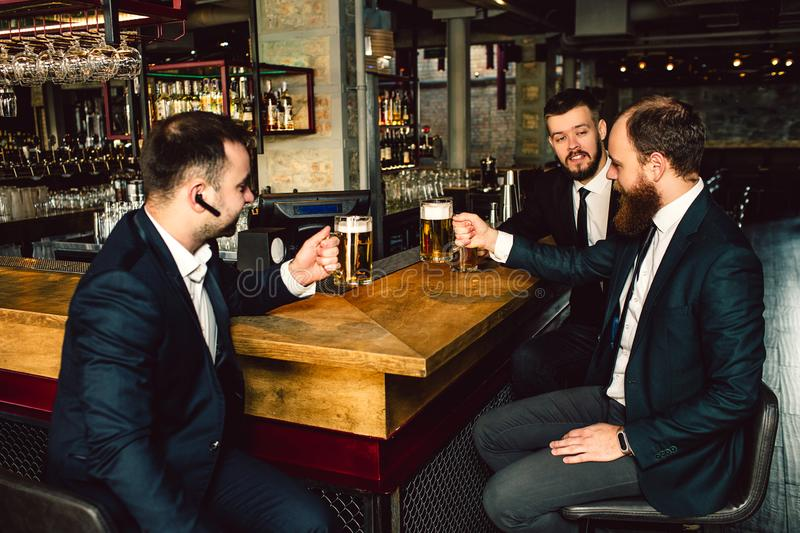 Three young businessman sit at table and hold cips of beer. They talk. People wear suits. First guy has black headphone stock image