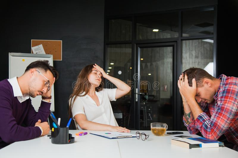 Three young businessmen have headache at office, sad failure royalty free stock photography
