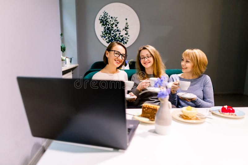 Three young Caucasian women using laptop, eating cakes with tea or coffee, together inside cafe.  royalty free stock images
