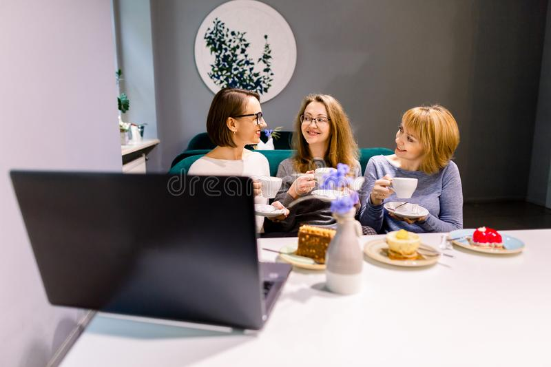 Three young Caucasian women using laptop, eating cakes with tea or coffee, together inside cafe.  stock images