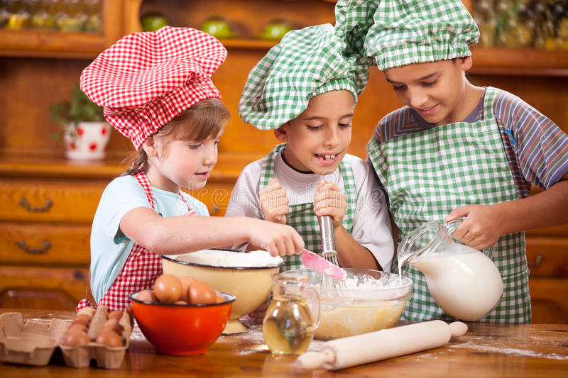 Three young child preparing ingredients for cookies in kitchen. Brother and sister in the kitchen preparing ingredients for cookies royalty free stock photos