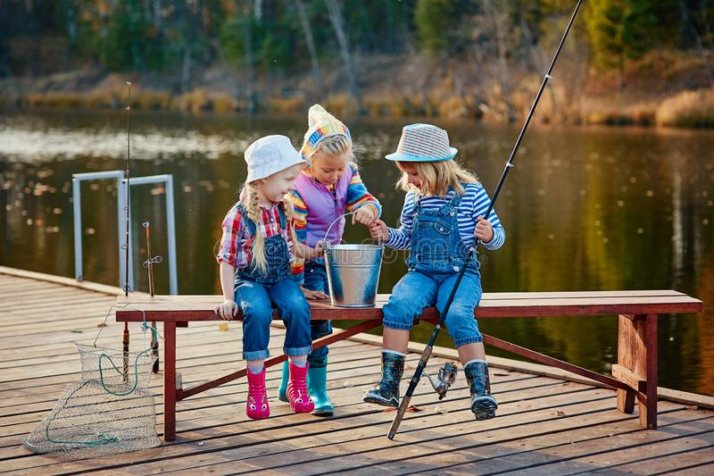 Three young children brag about fish caught on the bait. Concept of friendship and fun weekend or vacation stock photos