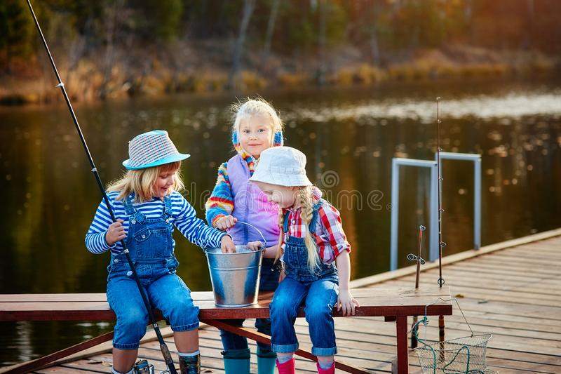 Three young children brag about fish caught on the bait. Concept of friendship and fun weekend or vacation royalty free stock images