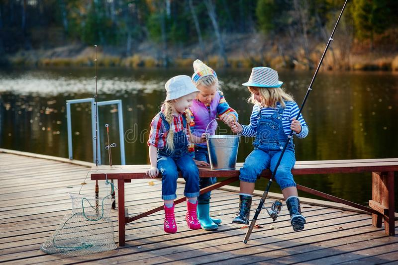 Three young children brag about fish caught on the bait. Concept of friendship and fun weekend or vacation stock image