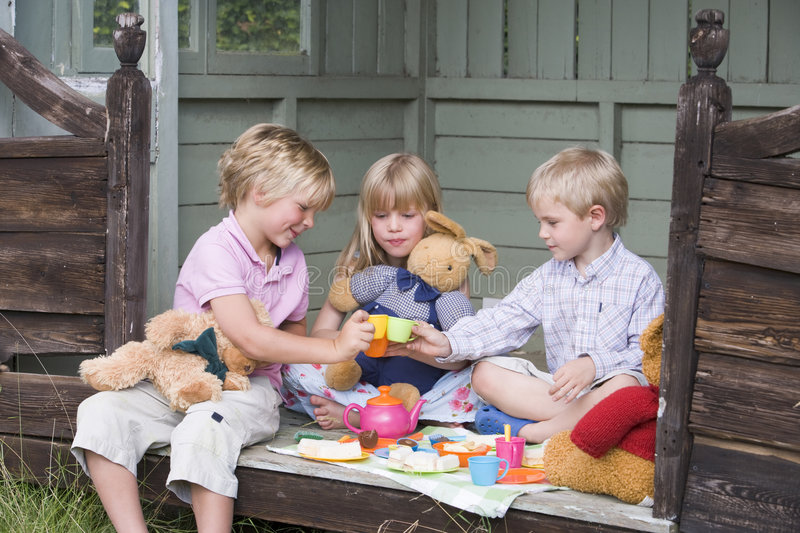 Three young children in shed playing tea royalty free stock photo