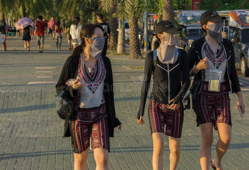 Three young Chinese women were walking up tthe beach for a small sightseeing tour royalty free stock photo