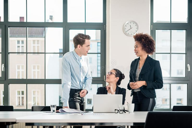 Three young colleagues talking during break in the meeting room royalty free stock photo