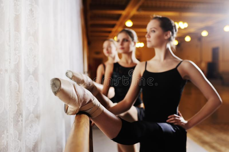 Three young cute ballerinas perform exercises on a choreographic machine or barre royalty free stock images