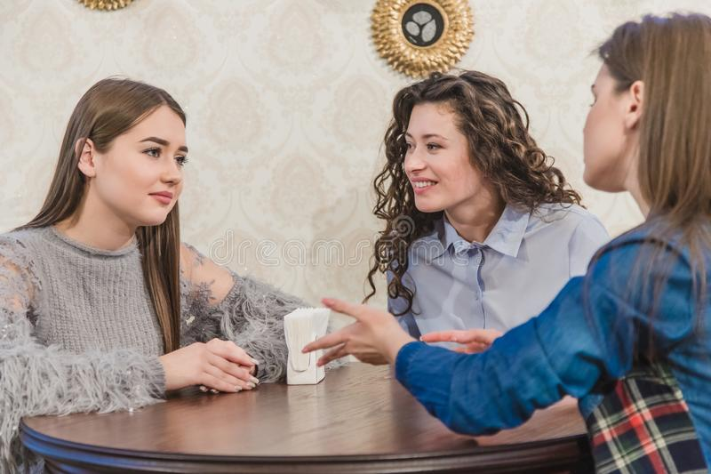 Three young cute girls met in a cafe. During this time, having ordered the cappuccino, they are waiting for their order. stock photos