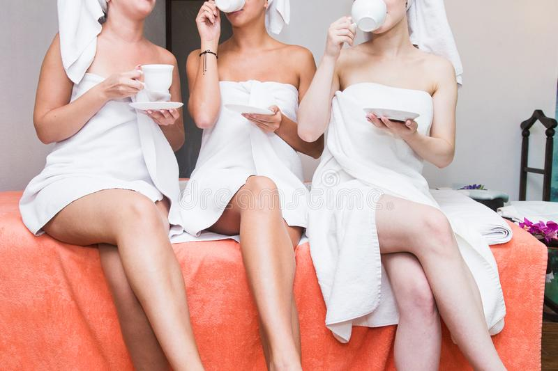 Three young cute girls in white bathrobes are drinking tea in the spa salon. Rest after sauna and beauty salon procedures. feet cl royalty free stock photography