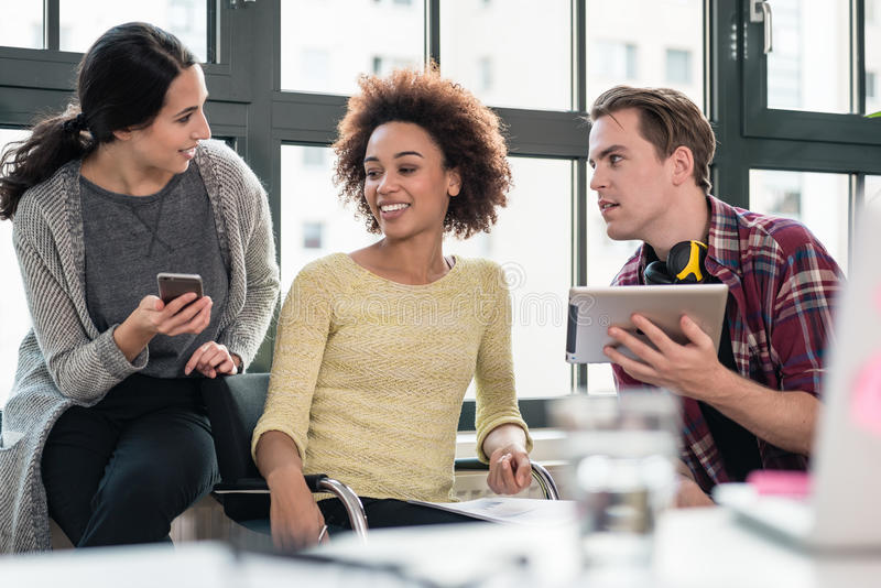 Three young employees using modern devices during break stock photos