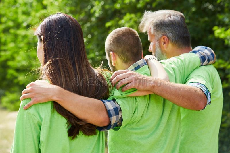 Three young environmentalists stand arm in arm. As a sign of teamwork royalty free stock photos