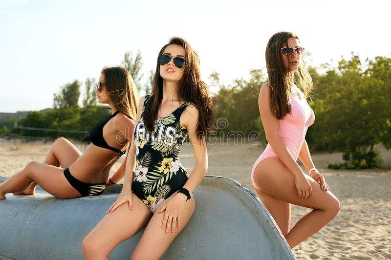 Three young fashionable lovely women relaxing on the beach in the sun. Pretty happy suntanned models wearing hot bikini stock photography