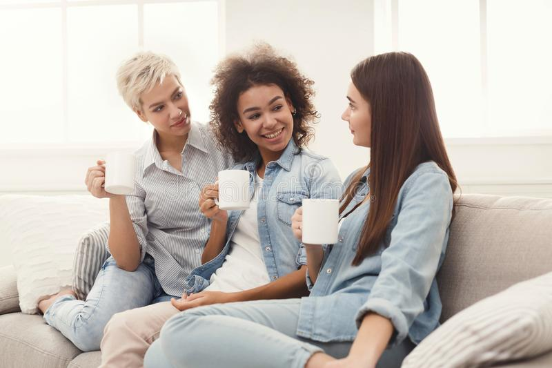 Three young female friends with coffee chatting at home royalty free stock photography