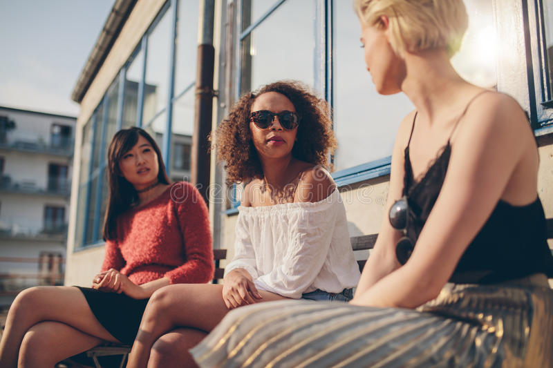 Three young female friends meeting outdoors. Multiracial group of young women sitting outdoors and chatting royalty free stock image