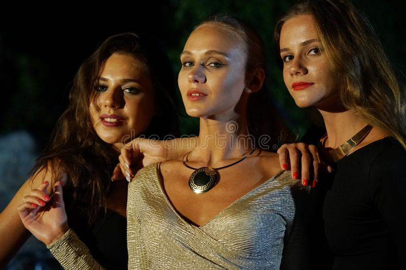 Friends in the nightclub. Three young female friends posing in the nightclub royalty free stock photo
