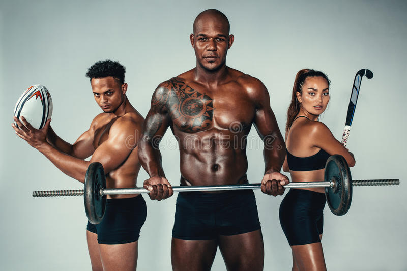 Three young fitness people with sports equipments stock images