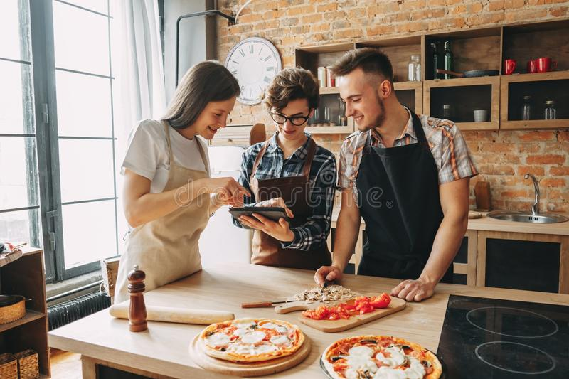 Three young friends cooking at kitchen together, reading recipe. At tablet pc. Culinary, togetherness, friendship concept stock image