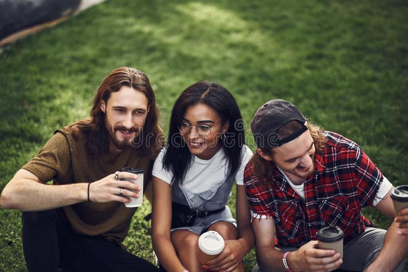 Three young friends enjoying coffee while sitting on the grass together royalty free stock image