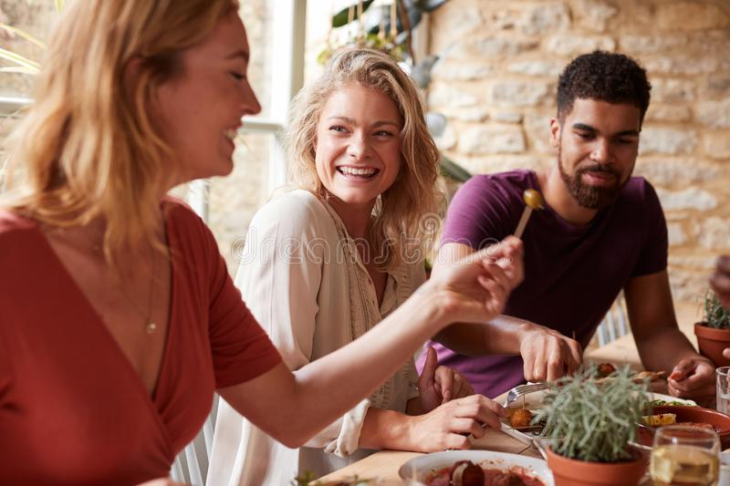 Three young friends having fun eating tapas at a restaurant royalty free stock photos